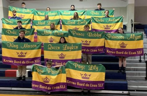 Carnival Ball maids and dukes show off their royal flags during the traditional King Cake Party for the senior court.